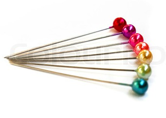 Seven colorful sewing pins on a white background